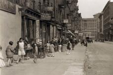Depression era street life with children playing and dancing in the street. Lots of vintage storefronts and two 1920 cars parked. 28th street looking east from Second Avenue. New York. April 1931. | Flickr - Photo Sharing!